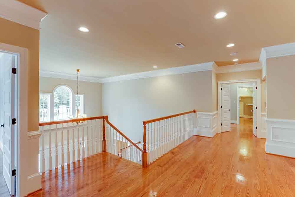 2nd story hallway with stairs, banister and several doors leading to rooms in Middleburg home