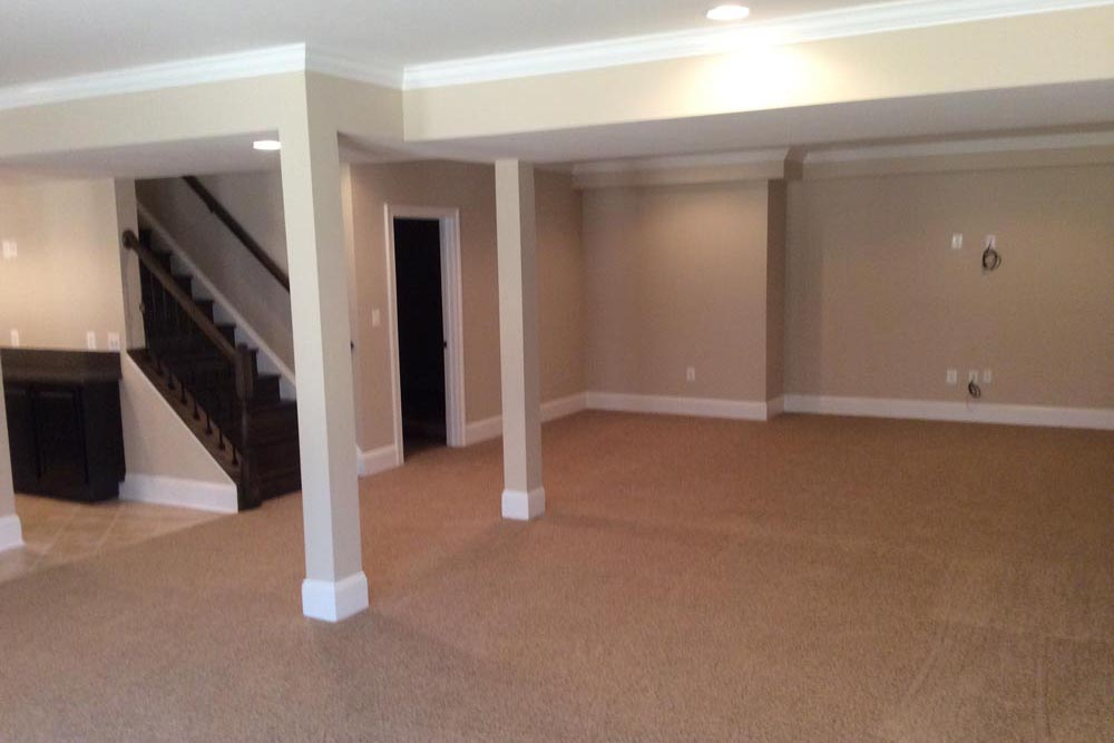 Angled version of large basement in Round Hill home with pillars, room, and stairs