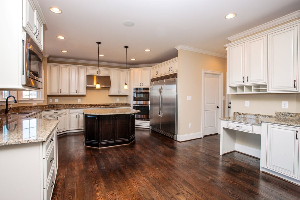 Angled view of Leesburg home kitchen with hanging lights, white cabients, microwave, and double door refrigerator