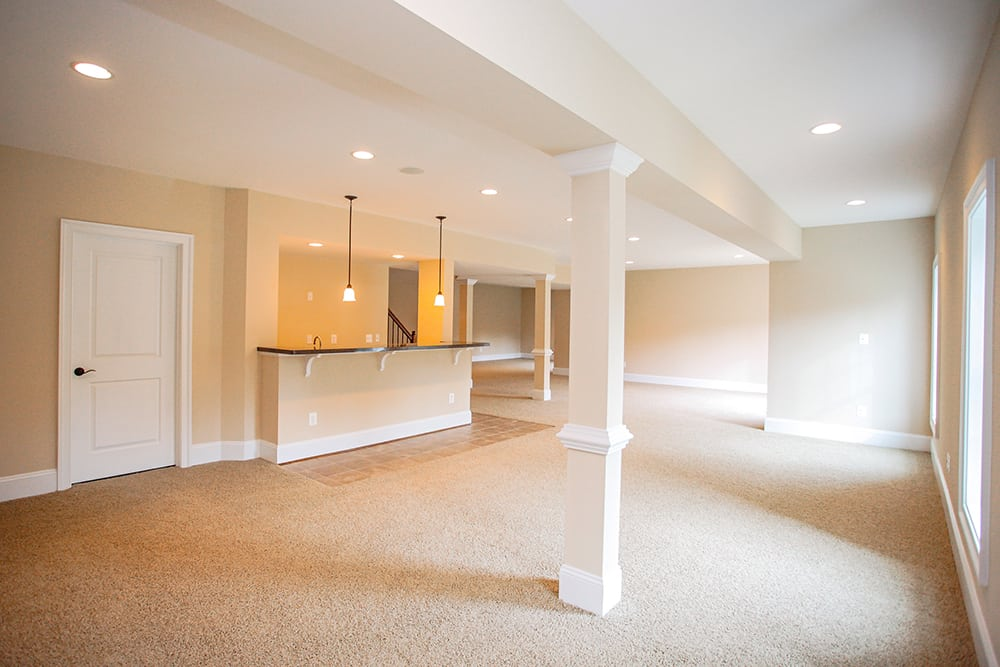 Angled view of Warrenton basement with hanging lights and bar