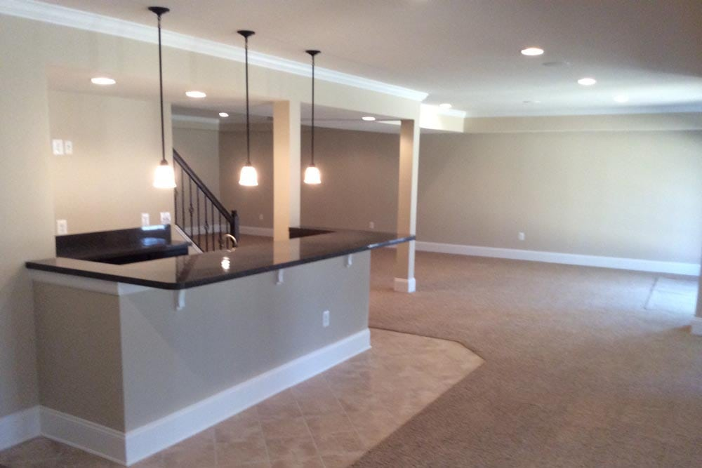 Angled view of basement bar with hanging lights in Round Hill home