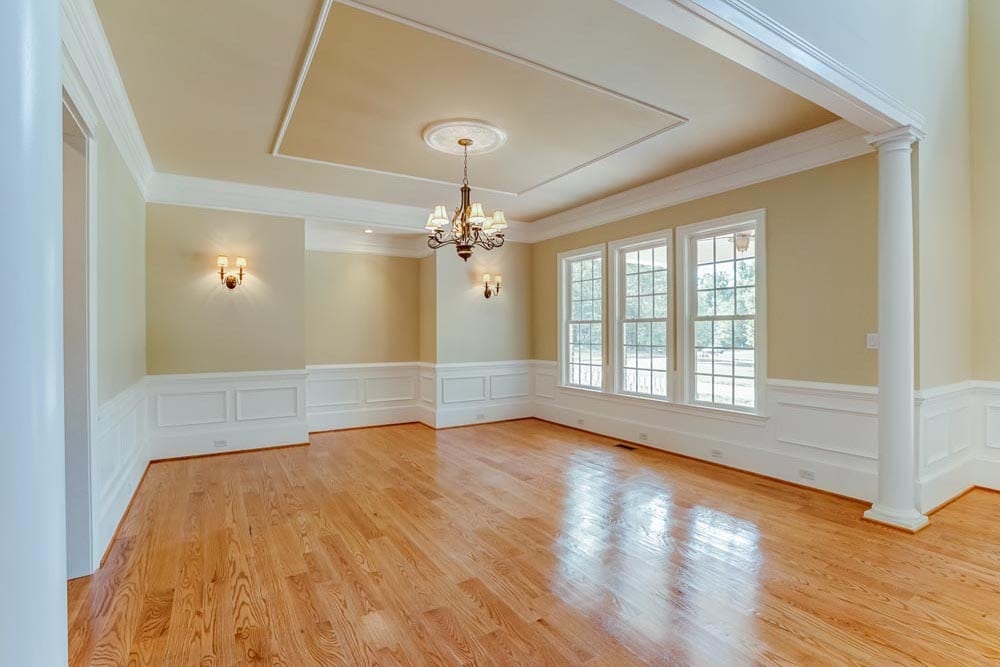 Angled view of dining room with chandelier and 3 windows in Middleburg home