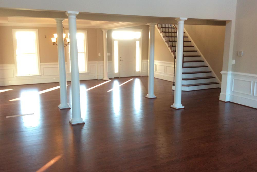 Angled view of house on The Plains lobby with dark brown stained wood floors, a ceiling fan, and pillars