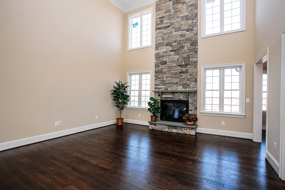 Angled view of two story open den with stone fireplace and windows