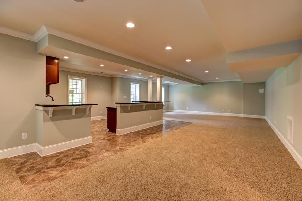 Basement bar split by entrance in home built by Stonehill Builders