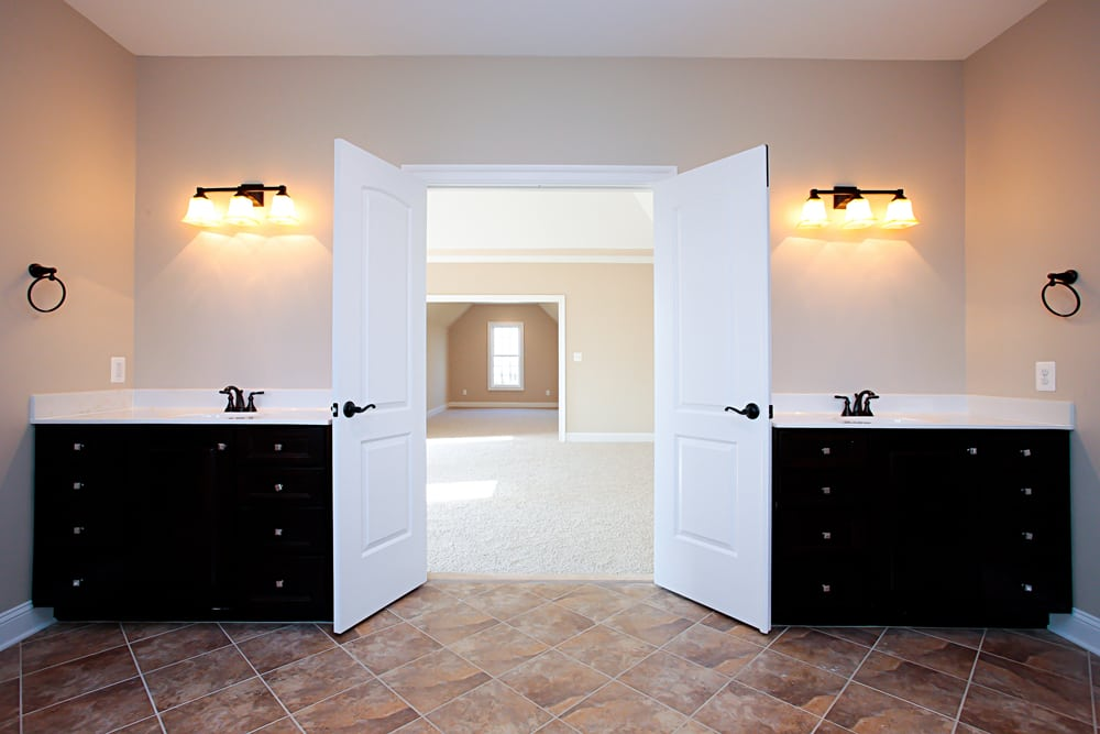 Bathroom in Nokesville home with white countertop sinks separated by double doors