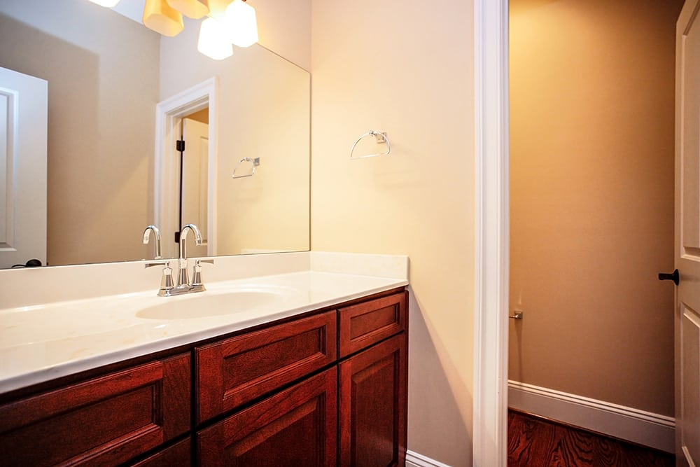 Bathroom in Warrenton house with stained cabinets and cream colored countertop