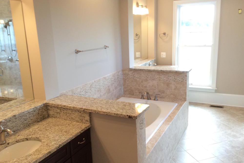 Bathroom with 2 granite countertop sinks separated by white bathtub in a house on The Plains