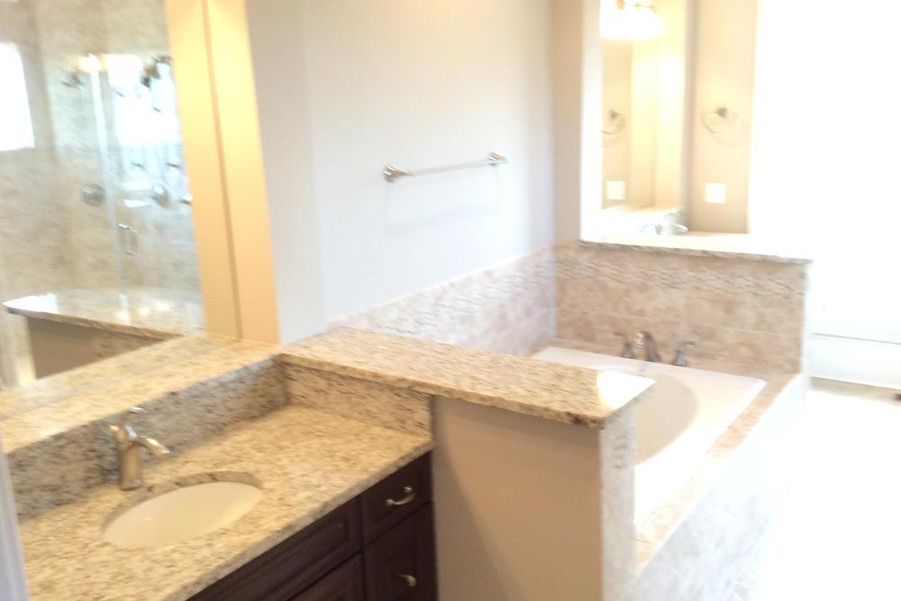 Bathroom with 2 granite countertop sinks with dark stained wooden cabinets separated by white bathtub in a house on The Plains