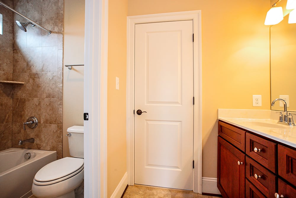 Bathroom with toilet between small wall and shower with sink in Warrenton house