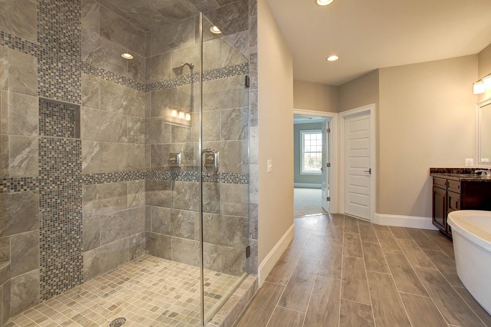 Bathroom with two sinks separated by bathtub with large gray stone shower in Culpeper home