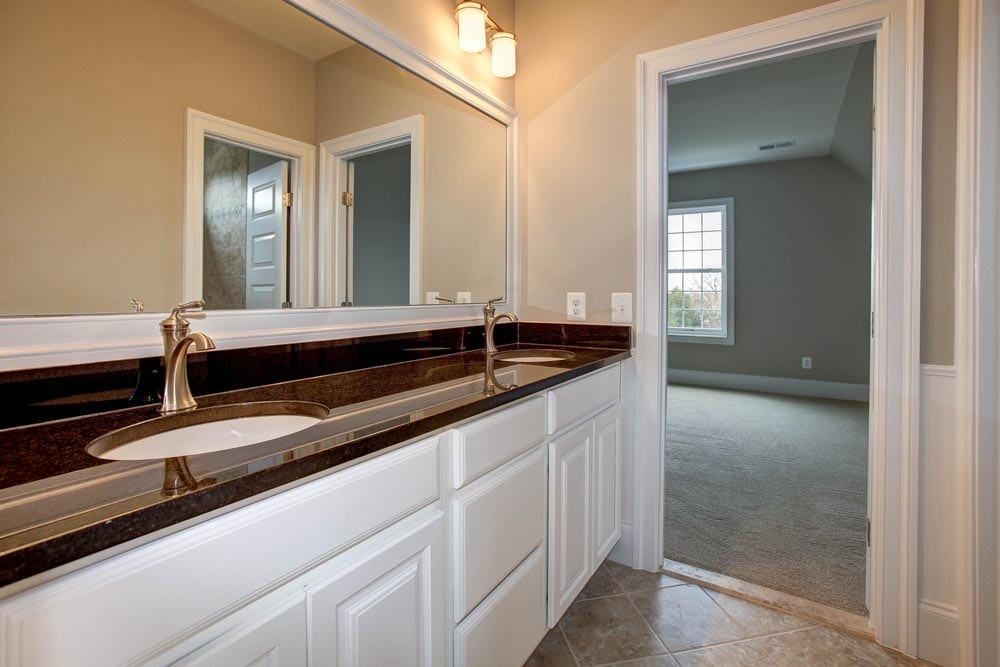 Bathroom with white cabinet sinks with light brown countertops in Culpeper home