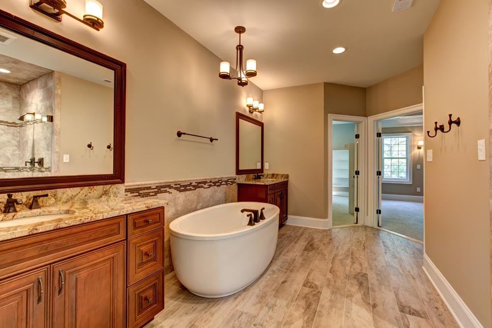 Bathtub and sink room leading to two other rooms