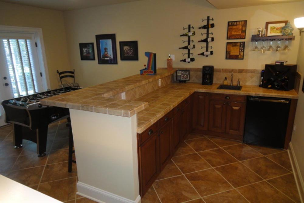 Behind Midlands home basement bar with mini-fridge and brown wood cabinets