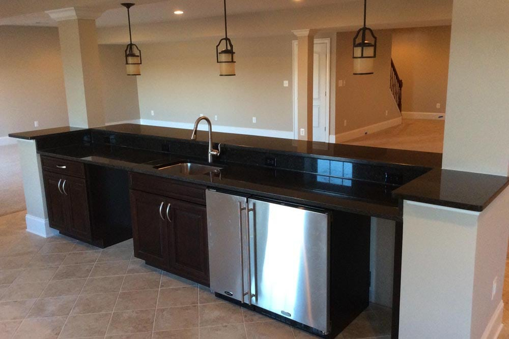 Behind The Plains home basement bar with dark brown cabinets, sink, and double door mini fridge