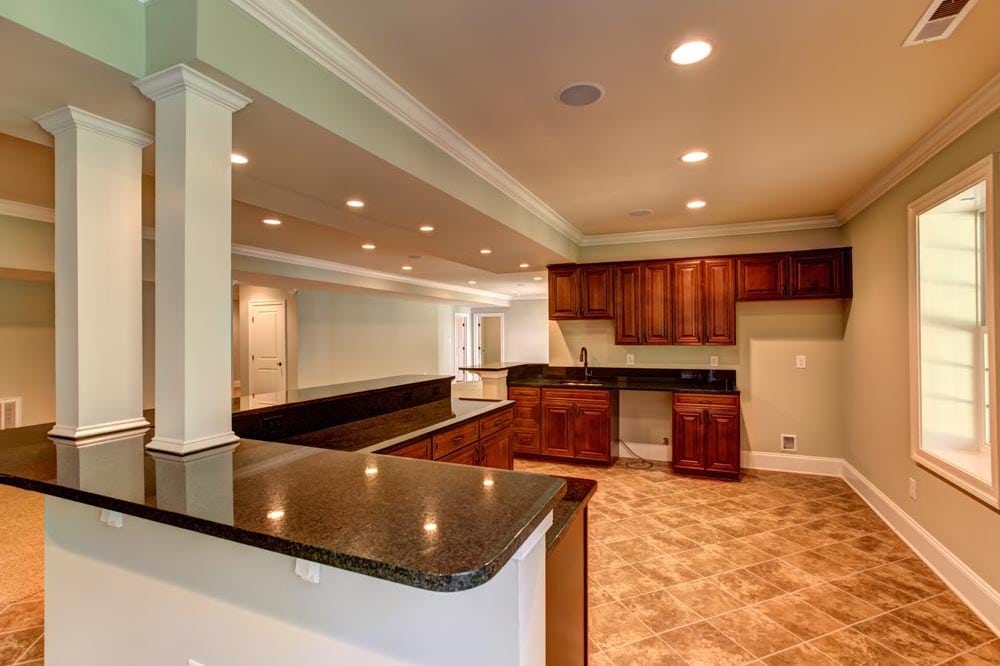 Behind bar with tiled floor and brown cabinets