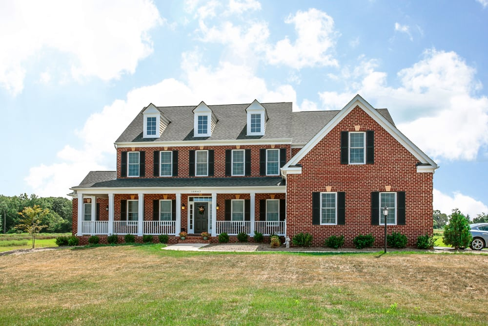 Brick front of Nokesville home with whtie porch, dark shingles, and dark shutters