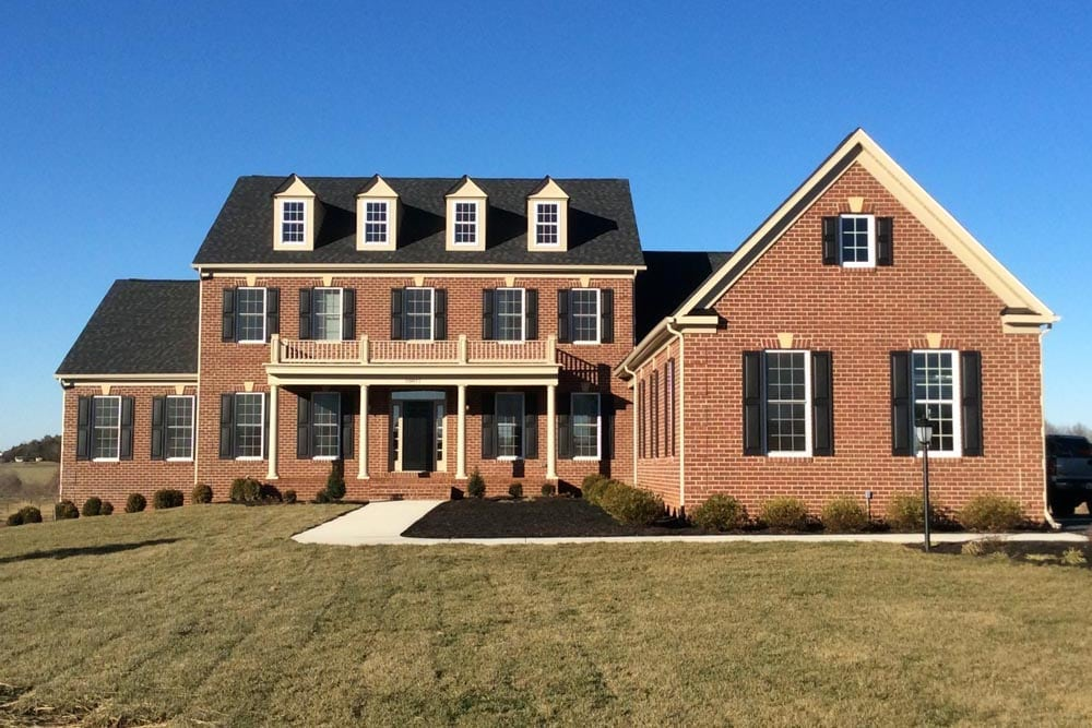 Brick front of house on The Plains with a 3 window balcony, dark shingles, and dark window shutters