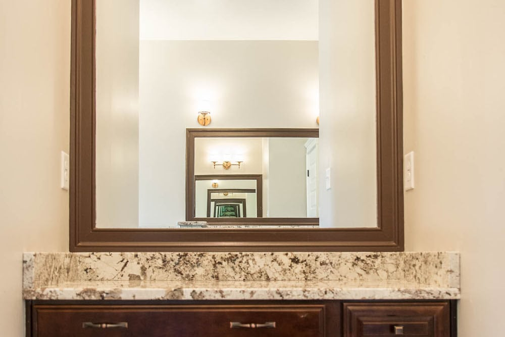 Cabinets and mirror with place for chair in Fairfax home
