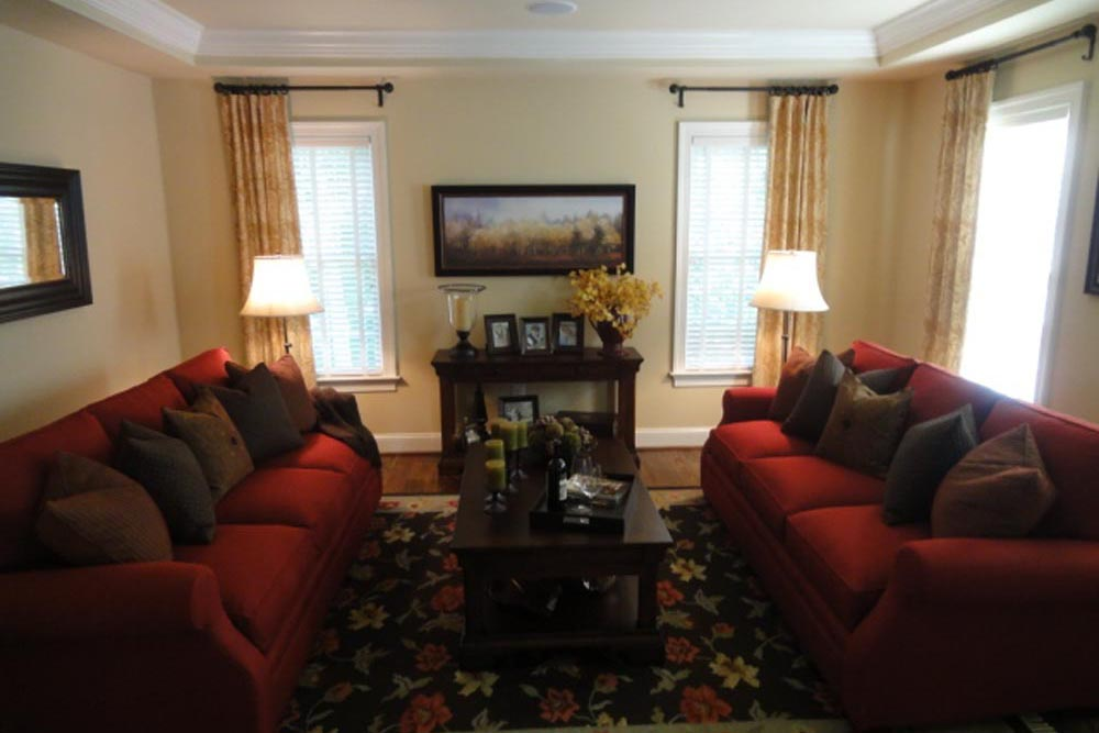 Closeup of Midland home living room with red couches and black ornamental rug