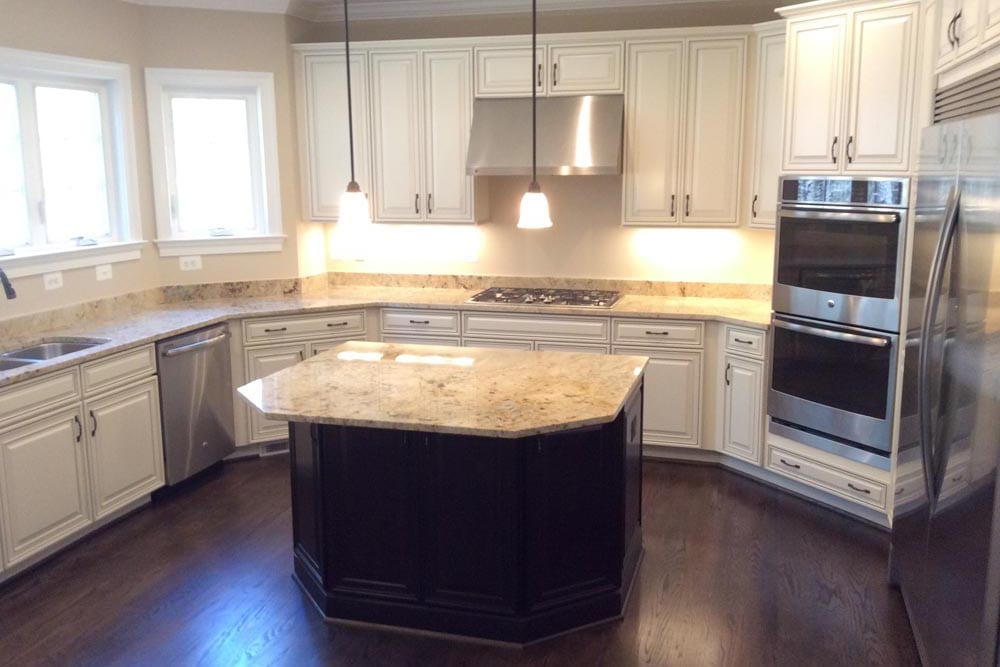 Closeup of Round Hill home kitchen island, double oven, stove, white cabinets, and double door refrigerator