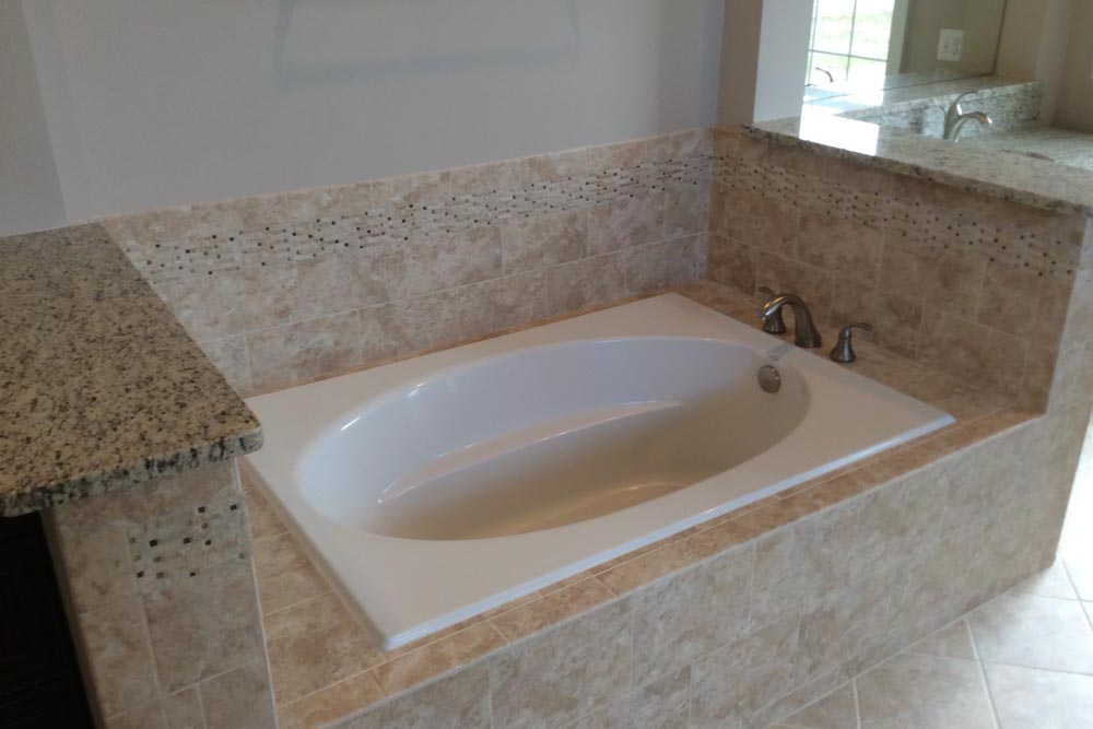Closeup of bathtub with low granite walls at the head and feet in a house on The Plains