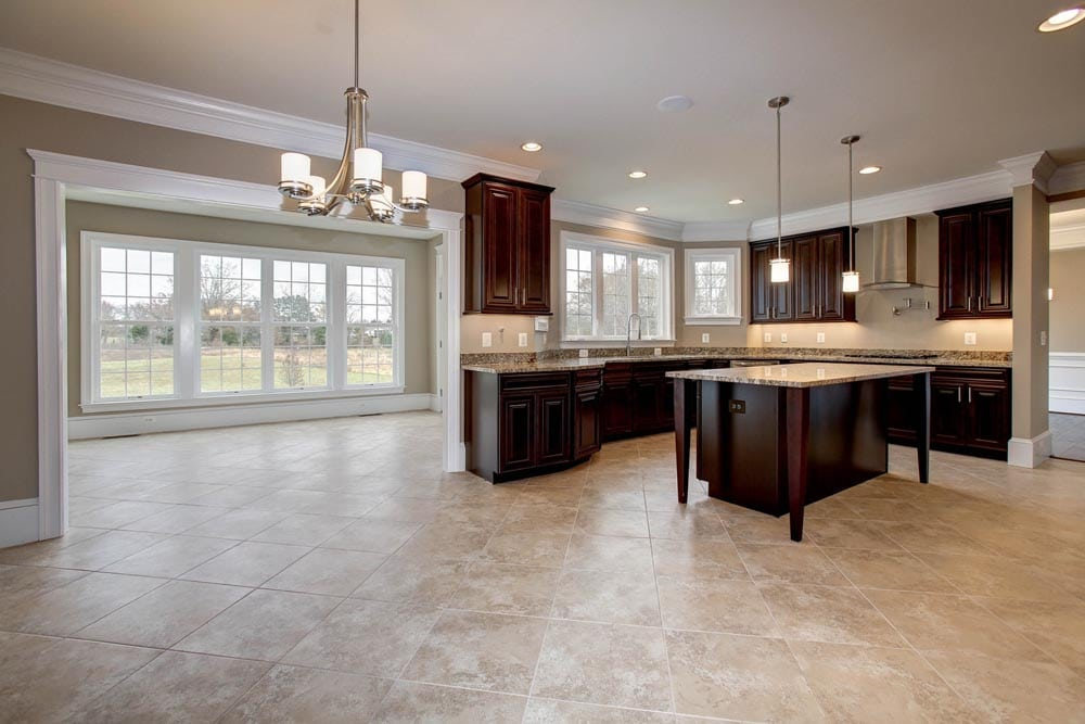 Culpeper kitchen with tile floors, brown wooden cabinets and island with chandelier and hanging lights
