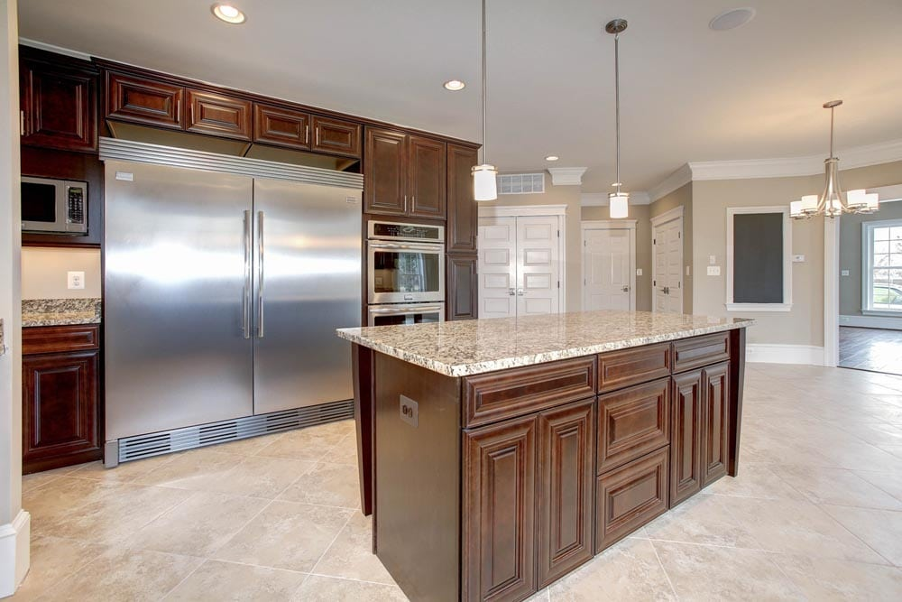 Kitchen with tile floors, brown wooden cabinets and island with double door refrigerator