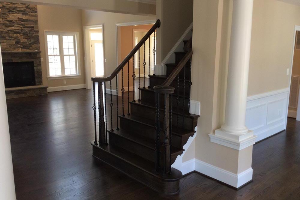 Dark brown stain front stairs with small pillar and stone fireplace in Round Hill home