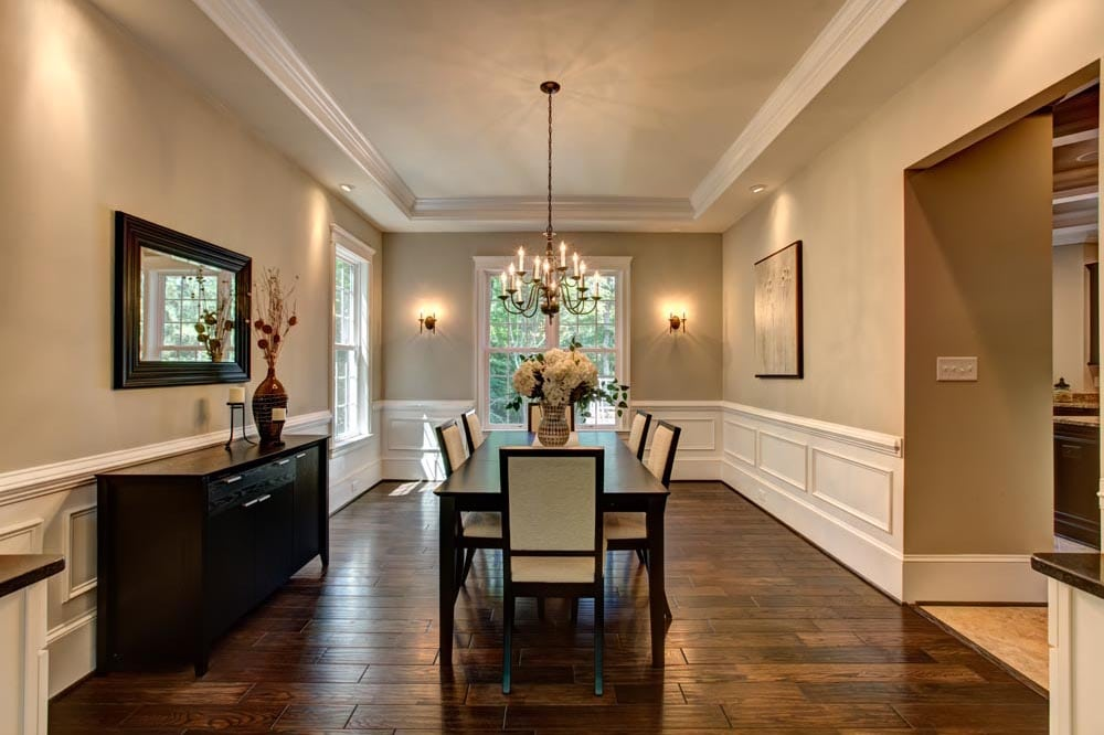 Dining room with chairs, table, and chandelier near windows