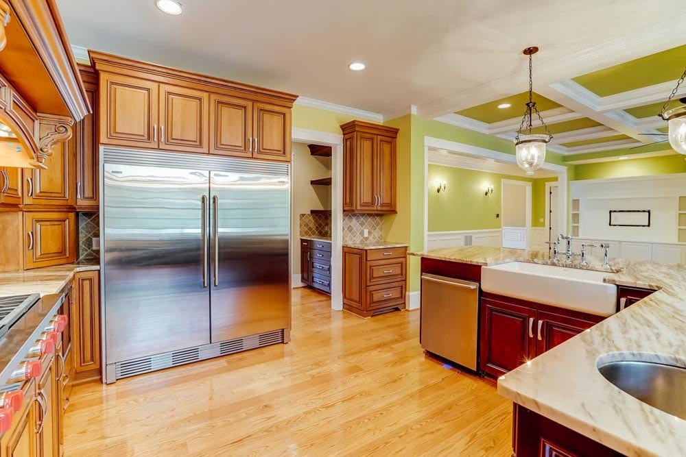 Double door refrigerator, dishwasher, and light stained cabinets in kitchen in Middleburg home