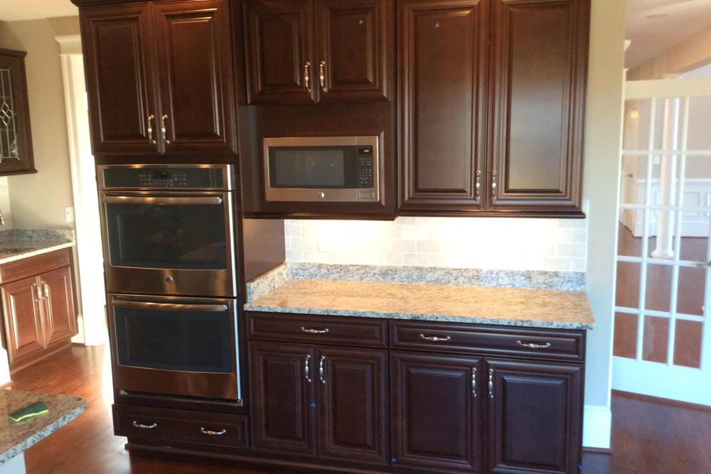 Double oven and microwave surrounded by brown cabinets with a granite countertop on the end in a house on The Plains
