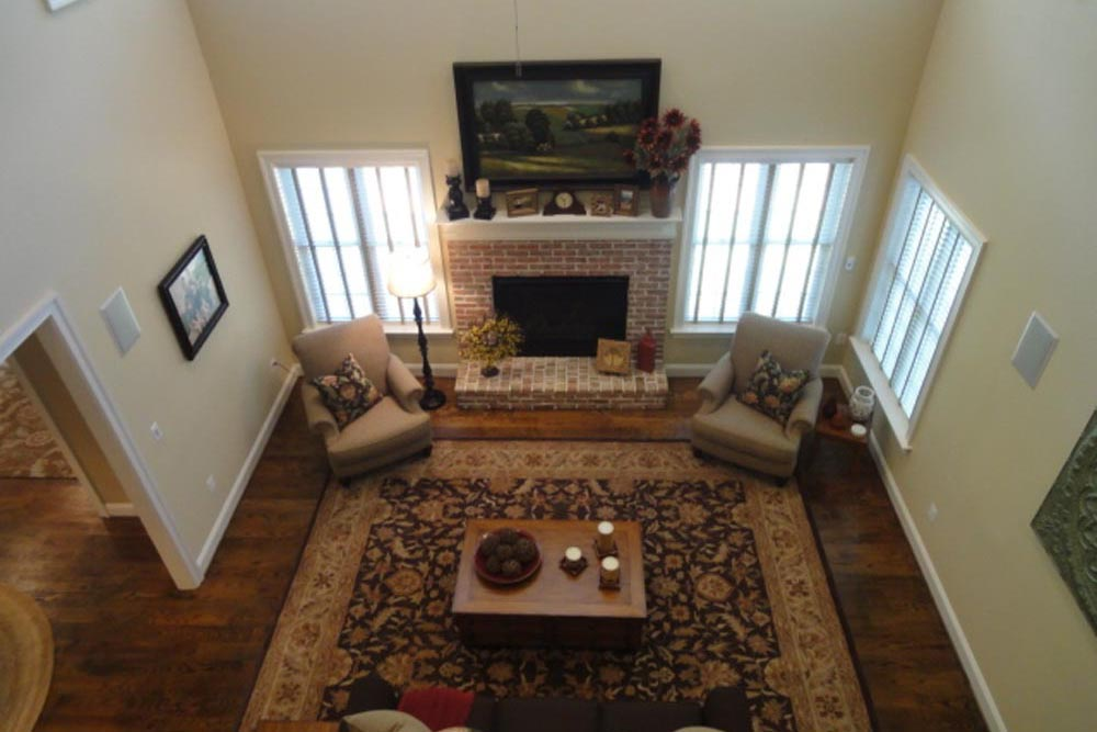 Downward view of Midland home living room with brick fireplace, rug, and chairs