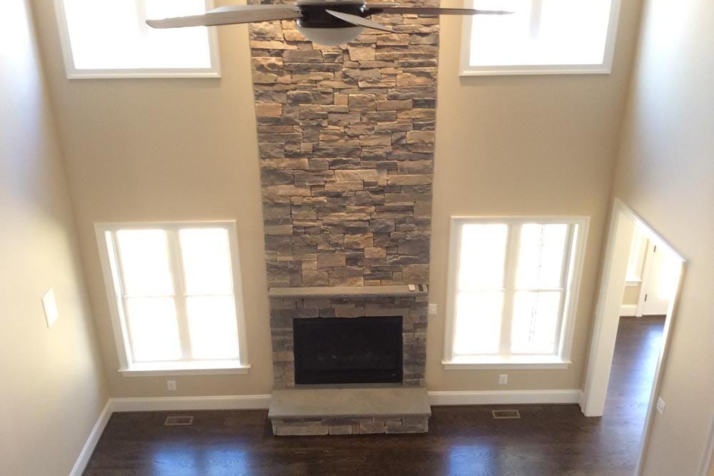 Downward view to first floor tall room with stone fireplace and fan