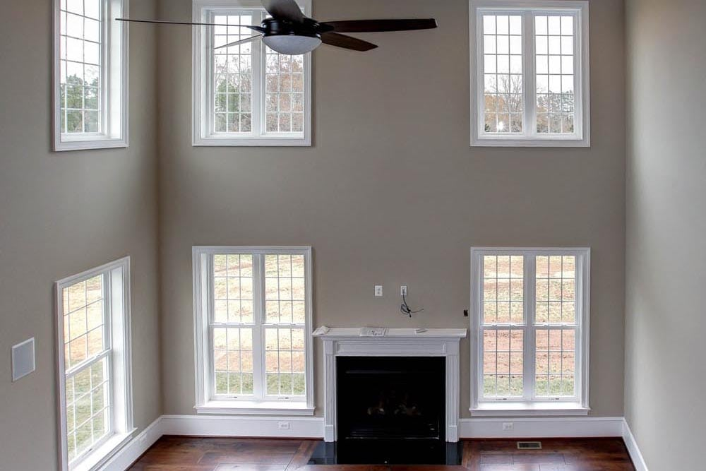 Far off photo of Culpeper home den with ceiling fan, dark brown wood floors, many windows, and stone fireplace
