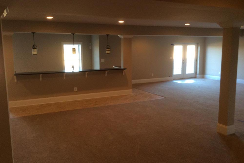 Far off view of long basement bar with hanging lights in a house on The Plains