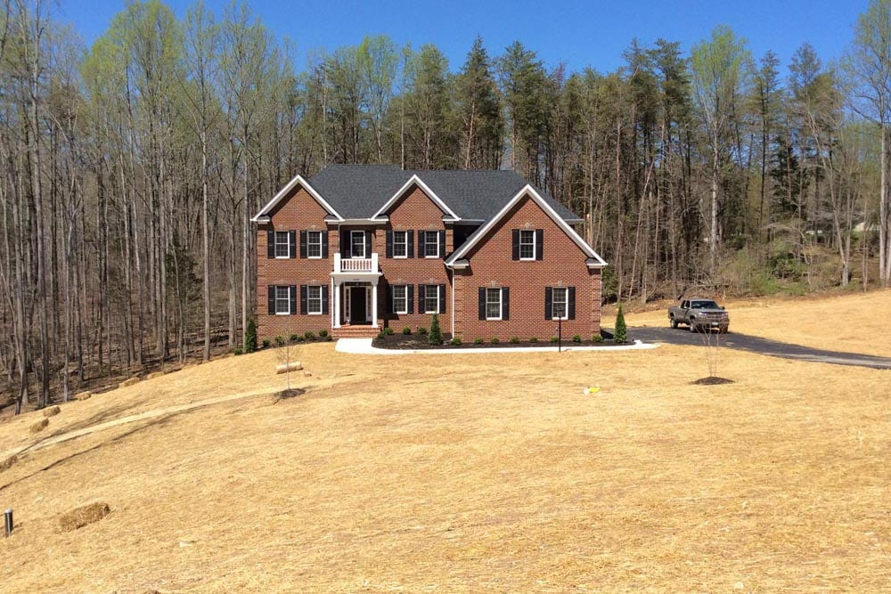Far off view of red brick Round Hill home with pine trees in the back