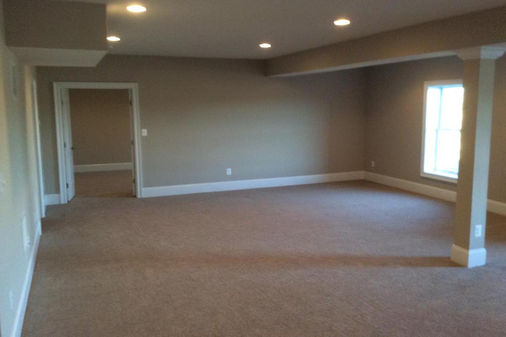 Far side of The Plains home basement with an adjacent room