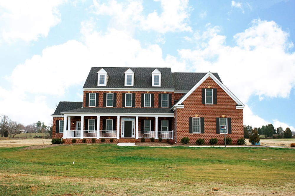 Front of beautiful Nokesville brick home with wrap around white porch and dark shingles