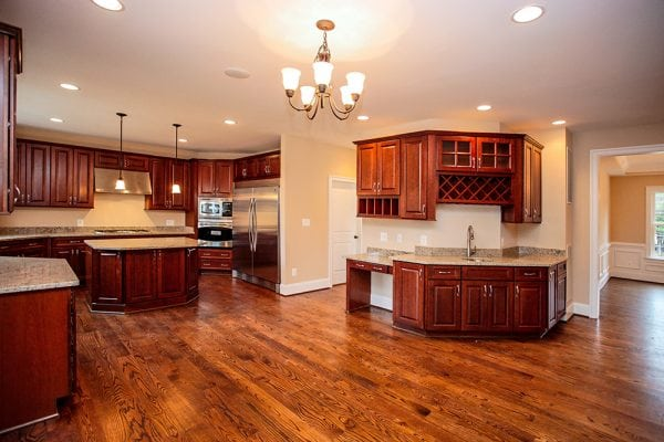 Full view of stained wood kitchen with chandelier inside a new home construction site in Warrenton