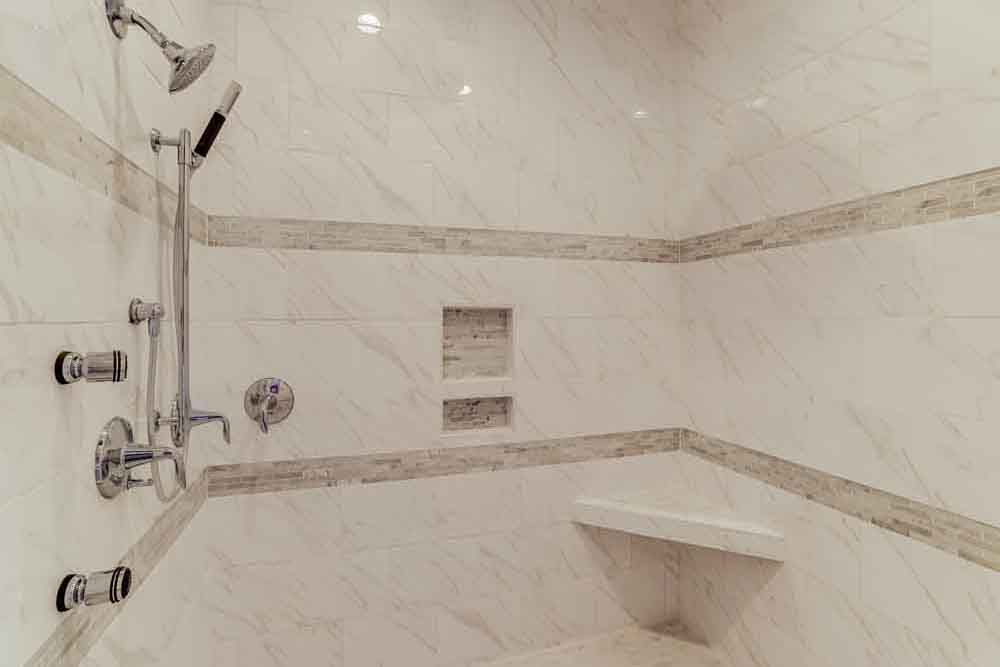 Gray stone master bathroom shower in Middleburg home with removable shower head
