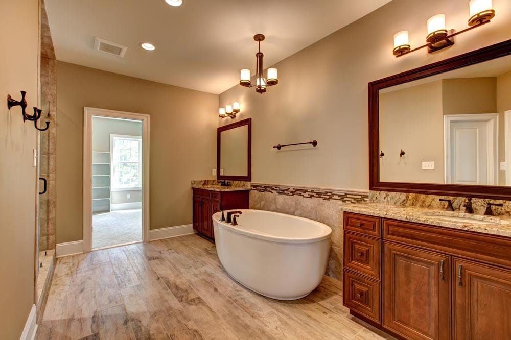 Grey slate bathroom with stand alone bathtub separating two sinks all facing shower