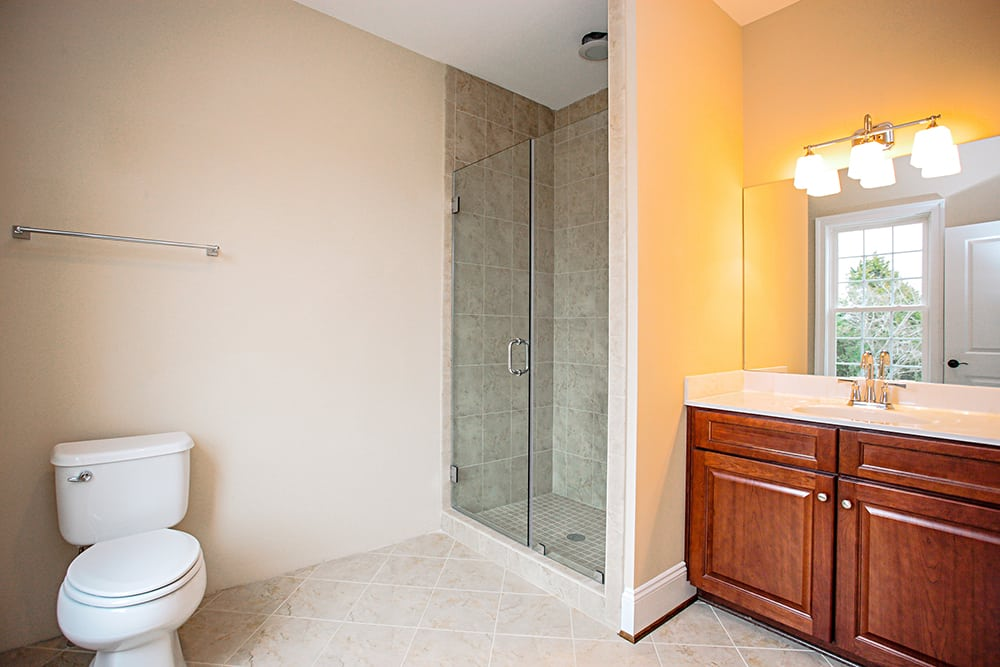 Guest bathroom with toilet, shower, and sink inside Warrenton house