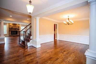 Interior stairs, fireplace, and room with full chandelier inside Warrenton house
