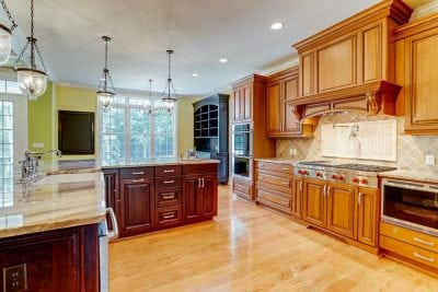 Kitchen with hanging lights and 2 different shades of stained wood cabinets in Middleburg home