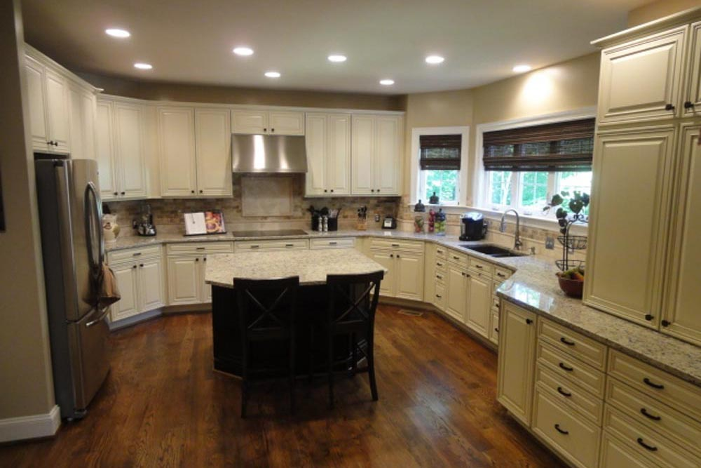 Kitchen with island and chairs, refrigerator, granite countertops, and white cabinets