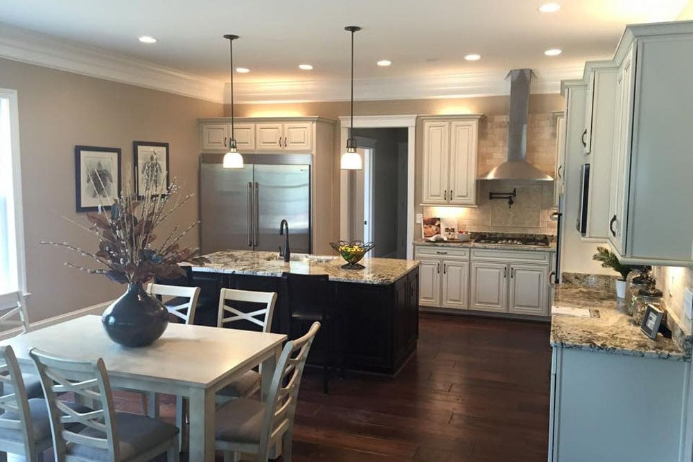Kitchen with island, double door refrigerator, and dining table in Fairfax home
