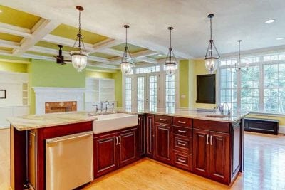 L-shaped kitchen island with hanging lights, dishwasher, and lightly stained cabinets in Middleburg home