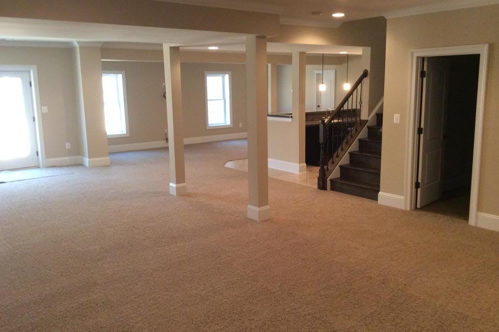 Large basement in Round Hill home with pillars and stairs