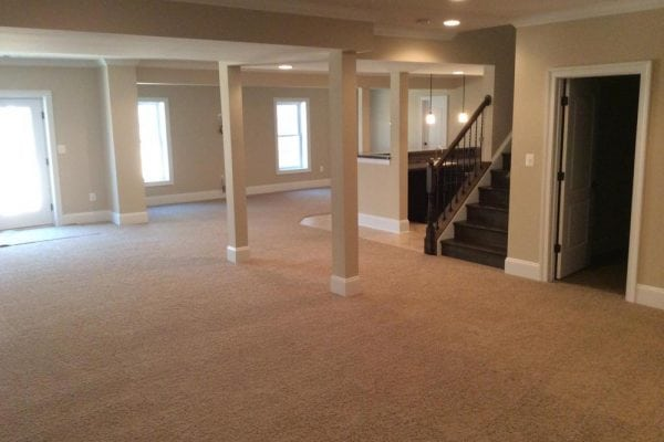 Large basement in Round Hill home with pillars, door to another room, and stairs